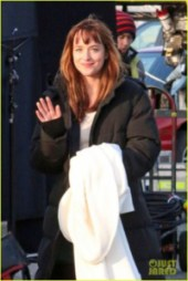 Dakota Johnson is all bundled up as she gives a wave after filming a scene for '50 Shades of Grey' in Vancouver